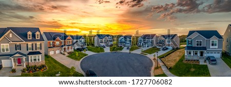 Cul de sac classic dead end street surrounded by luxury two story single family homes in a new residential East Coast USA real estate development neighborhood with dramatic colorful sunset sky
