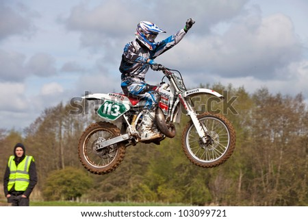 CULHAM, ENGLAND - MAY 5: Moto-X rider Ben Milward punches the air mid jump as he approaches the finish line in first place at the Culham Park vintage moto-X gala on May 5, 2012 at Culham
