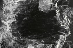 Culinary abstract background of scattered flour on a black wooden background.