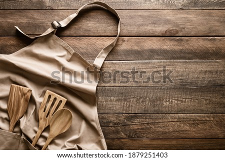 Culinary background, kitchen utensils and apron on kitchen countertop with blank space for any recipe or menu text