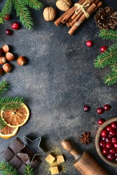 Culinary background with christmas winter spices and ingredients for baking on a dark slate, stone or concrete table. Top view with copy space.