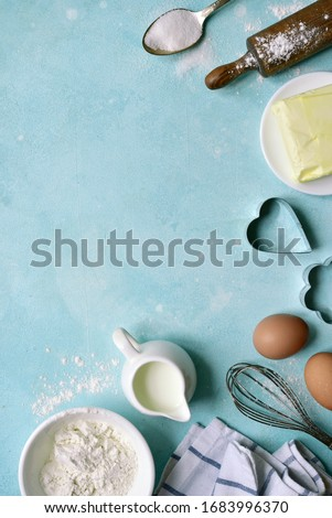 Culinary background with ingredients for baking : flour, butter, eggs, milk and sugar on a light blue slate, stone or concrete table. Top view with copy space.