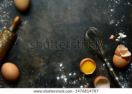 Culinary background with ingredients for baking : milk, butter,sugar, dough and egg on a dark slate, stone or concrete table. Top view with copy space.
