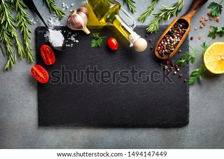 Culinary background with kitchen slate board and aromatic spices. Empty place for menu or recipe. Top view.