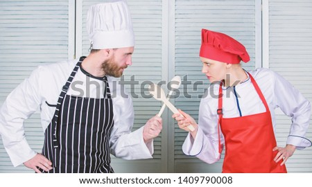 Culinary battle of two chefs. Couple compete in culinary arts. Kitchen rules. Culinary battle concept. Woman and bearded man culinary show competitors. Who cook better. Ultimate cooking challenge.