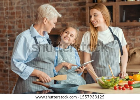 Culinary blog. Cute little girl showing granny and mom new culinary recipes on digital tablet, kitchen interior