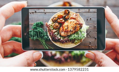Culinary blog. Home cooking hobby. Food recipe. Closeup of female hands taking picture of roasted meat with grilled mushrooms.