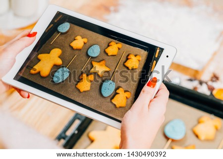 Culinary blog. Top view of tablet screen. Lady taking picture of colorful biscuits on sheet pan.