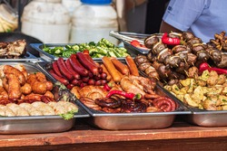 Culinary Buffet with healthy take away meal - grilled vegetables, fish and meat on the street food culinary market, festival, event.  Different types of delicious meat. Outdoor Cuisine.