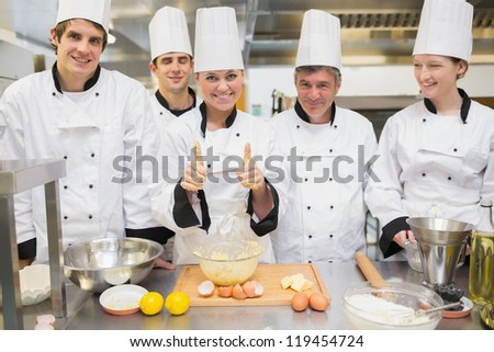 Culinary class with pastry teacher giving thumbs up in kitchen