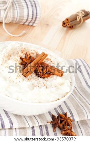 Culinary rice pudding with cinnamon and star anise garnish in white bowl. Delicious vegetarian food.