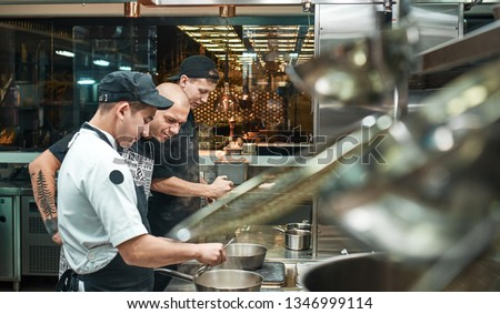 Culinary school. Strict young chef in apron looking carefully how his assistant cooking at restaurant kitchen #1346999114