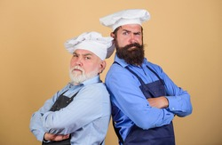 Culinary show. Restaurant staff. Culinary battle. Mature bearded men professional restaurant cooks competitors. Chef men wear aprons. Father and son culinary hobby. Cafe workers. Culinary industry
