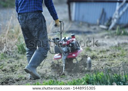 Cultivators driving in the vegetable garden #1448955305