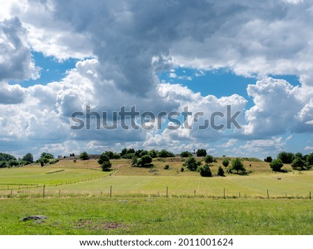 Cultural grass landscape with burial mounds from the viking age and fields and fences. Dramatic clouds in the sky. Stones and trees scattered in the scene.  Shot in Birka, Sweden, Scandinavia Stock fotó ©