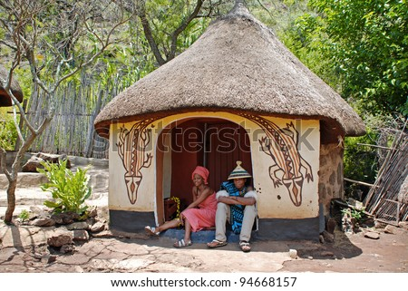 CULTURAL VILLAGE LESEDI,SOUTH AFRICA-JANUARY 1: An unidentified African sotho couple in handmade dress sitting near native tribal house on January 1,2008. Sotho are distinguished by colorful blankets and conical hats.