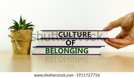 Culture of belonging symbol. Books with words 'culture of belonging' on beautiful white background. Businessman hand. Business, culture of belonging concept. Copy space.