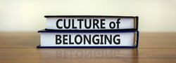 Culture of belonging symbol. Books with words 'culture of belonging' on beautiful wooden table, white background. Business, culture of belonging concept. Copy space.