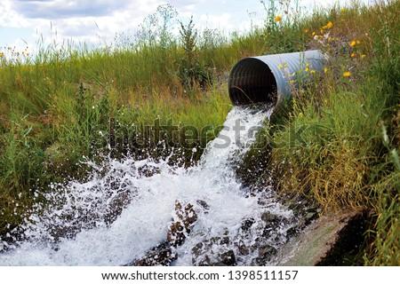 Culvert Spilling Water Splashing out in Grass