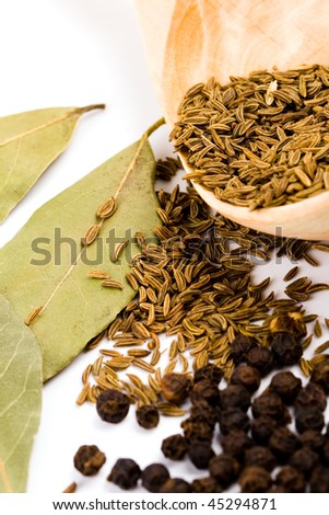 cumin on wooden spoon, black pepper, and bay leaves on white background - stock photo