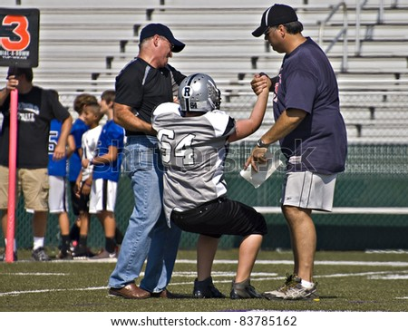 CUMMING, GA - AUGUST 27: Unidentified injured player helped off the field during a game of 11-13 year-old boys, August 27, 2011 in Cumming GA. The Raiders vs The War Eagles.