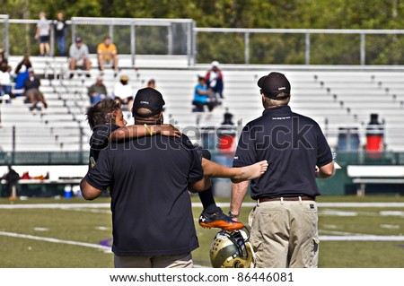 CUMMING, GA - OCTOBER 8 : Unidentified injured player being carried off the field by coaches during a football game; the Raiders vs the Saints, on October 8, 2011 in Cumming, GA.