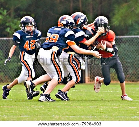 CUMMING, GA - SEPTEMBER 12: Unidentified players make a tackle during a Broncos vs.The Eagles recreational football game on September 12, 2009 in Forsyth County, Cumming, GA. The game is part of the local Recreation Department Football Program.