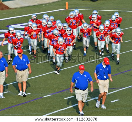CUMMING, GA/USA - SEPTEMBER 8: A 7th grade football team and coaches on the field.  September 8, 2012 in Cumming GA. The Wildcats  vs The Mustangs.