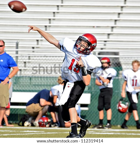 CUMMING, GA/USA - SEPTEMBER 8: Unidentified boy throwing a pass during a football game. A team of 7th grade boys September 8, 2012 in Cumming GA. The Wildcats  vs The Mustangs.