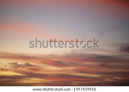 Cumulus sundown clouds with sun setting down on dark background #1497429416