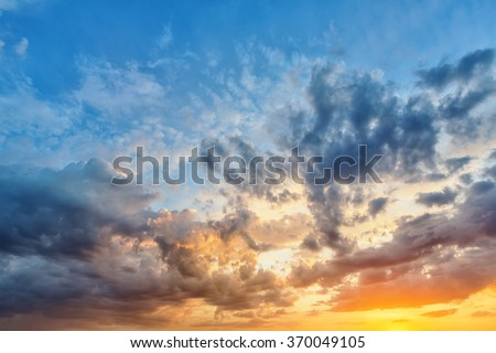 Cumulus sunset clouds with sun setting down #370049105