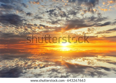 Cumulus sunset clouds with sun setting down #643267663