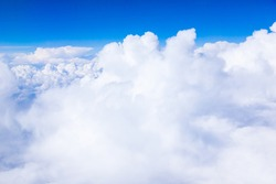 Cumulus white clouds and blue sky from the height of an airplane.
