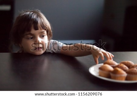 Cunning cute little girl stealing delicious muffin on table, hungry funny impatient child reaching hand to take homemade cookies from plate, unhealthy food and kids sugar craving addiction concept