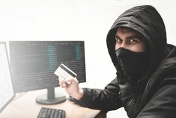 Cunning hacker fraudster in white background with stolen credit card in hand tries to steal money from bank account. Internet theft concept