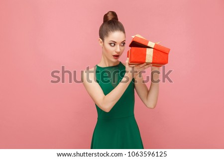 Cunning woman unboxing red gift box looking inside. Expression emotion and feelings concept. Studio shot, isolated on pink background