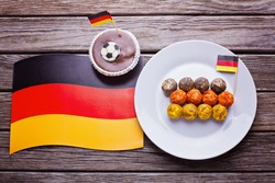 Cup cake with football icon and german flag with plate with cheese ball in color of german flag  with german flag on table