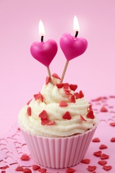 Cup cake with heart candles on pink background