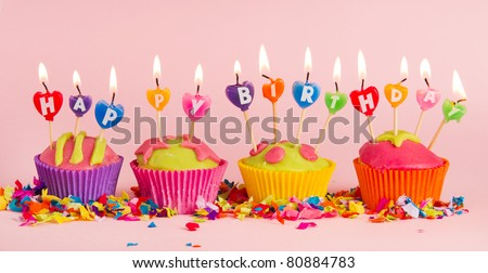 Cup cakes with burning happy birthday candles - stock photo