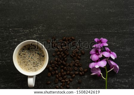 Cup coffee, roasted coffee bean and orchids on grungy tile textured. Copy Space.