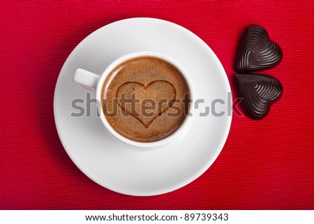 cup coffee with heart and chocolate candies on a red napkin background ,