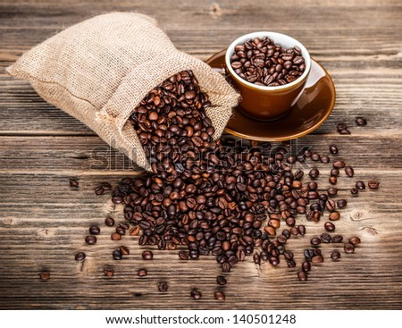 Cup full of coffee beans with sack - stock photo