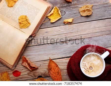 Cup hot cappuccino coffee on wooden table with autumn leaves ,book.Autumn concept.Warm autumn picture .Selective focus.Copy space.top view #718357474