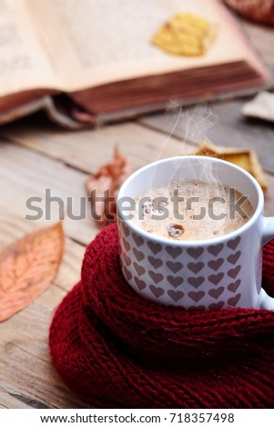 Cup hot cappuccino coffee on wooden table with autumn leaves ,book.Autumn mood concept.Warm autumn picture .Selective focus.