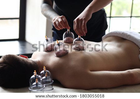 Cup massage. Massage vacuum banks. Close-up of man lying with banks on his back in spa salon. Vacuum banks in treatment and cosmetology. Vacuum therapy.