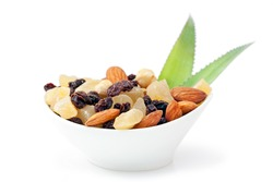 Cup of a variety of tropical dried fruits including nuts and raisins on white background with fresh leaves of pineapple