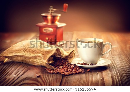 Cup of aromatic coffee on saucer with sack full of roasted coffee beans and coffee mill on wooden table. Cup of warm coffee with burlap bag with coffee grain over vintage wooden background. Espresso