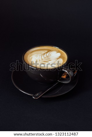 Cup of art latte on a cappuccino coffee isolated on black background #1323112487