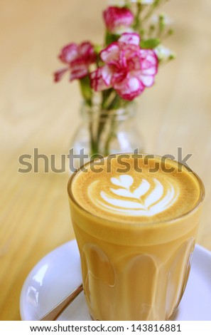 Cup of art latte or cappuccino coffee with flower