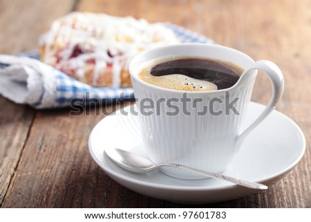 Cup of black coffee and cinnamon roll